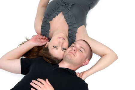 smooching: Beautiful couple relax by laying on the floor close together   Both are unsmiling and cheek to cheek   She is wearing grey and he is wearing black