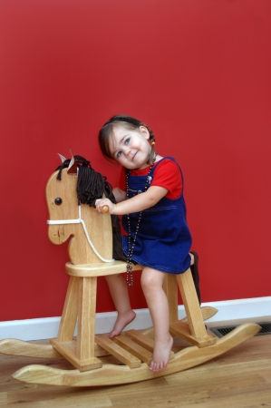 Little girl rides her wooden rocking horse and dreams of one day having a real horse   Walls are deep red and little girl is wearing a red shirt and denim overall   Her eyes are skyward as if asking for a horse  Stock Photo