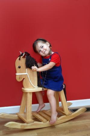 overall: Ni�a que monta su caballo mecedora de madera y sue�a con tener alg�n d�a un caballo de verdad paredes son de color rojo y ni�a lleva una camisa roja y jeans generales Tiene los ojos hacia el cielo como si estuviera pidiendo un caballo