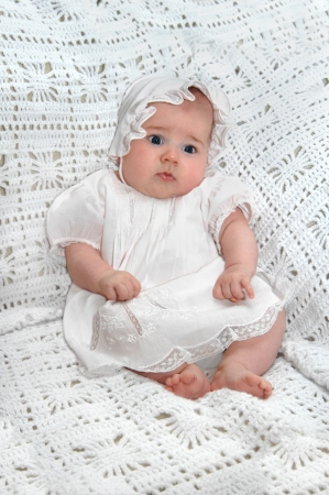 Beautiful infant girl wears a bonnet and frilly dress   She is awake and staring amazed at her new world