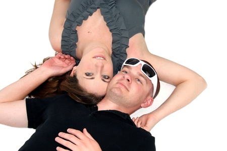 high angle shot: High angle shot shows couple laying on an all white floor, cheek to cheek   Man is wearing sunglasses on his head