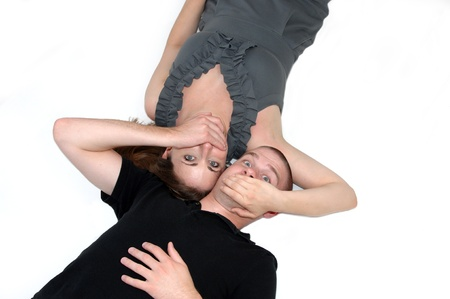 eyes shut: Couple lay in an all white room with heads close together   They have their hands over each other Stock Photo