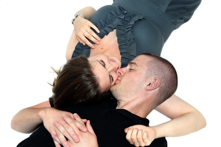 smooching: Young man and woman lay on all white floor close to each other   The man kisses her on the cheek and she is smiling   He is wearing a black shirt and she has on a gray dress