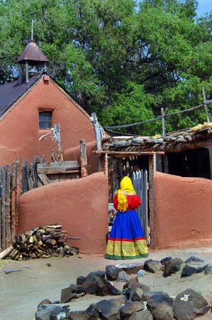 Costumed, female enactor enters rustic wooden courtyard of historic church at El Rancho De Las Golondrinas historic park in New Mexico.  Costume is bright red and yellow. photo