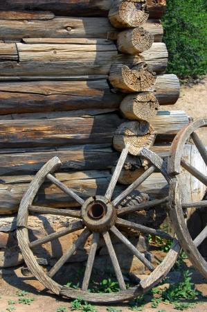 carreta madera: Dos ruedas de carro r�stico apoyarse en una pared de la cabina de registro en el El Rancho de las Golondrinas National Historic Trail.