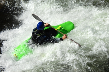 Whitewater challenges kayaker on a river in North Carolina   Paddle raised, man tackles boiling river surrounding him   Kayak is brilliant green