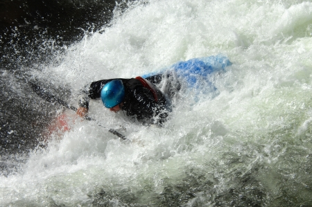 kayaker: Kayaker is swamped by raging whitewater on a river in North Carolina   His kayak is blue and his helmet is blue    Stock Photo