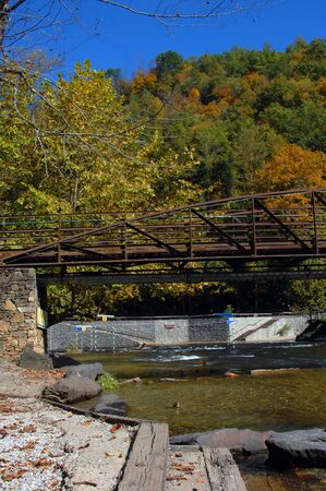 Kayak obstacle course is surrounded by Autumn color   Bridge spans river and obstacle course poles and flags hang suspended over water