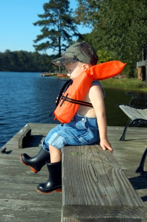 safe water: Small boy sits on a wooden dock wearing a water safety vest   He is wearing rubber galoshes and overalls   His tongue is between his lips as if tasting his fish dinner that he will catch                             Stock Photo