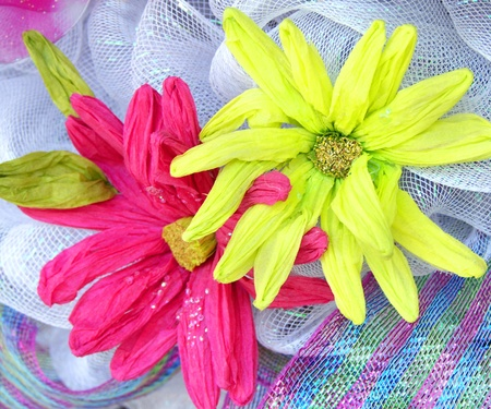 hand crafted: Two paper daisies decorate hand made wreath   One flower is neon green and the other is hot pink  Stock Photo