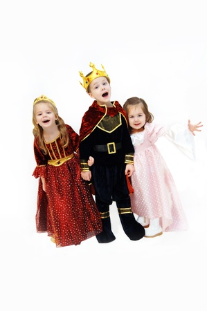 King, queen and princess are laughing and talking as they pose in their Halloween costumes.  Children are wearing crowns, gowns and royal cape. Stock Photo