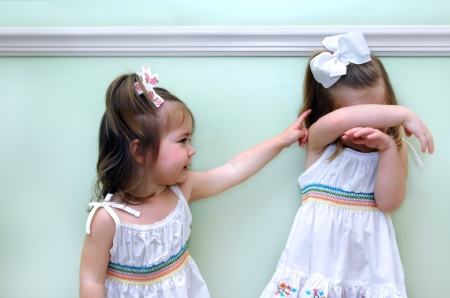 shaming: Baby sister teases older sister with an accusing finger   Big sister covers her head upset and distressed