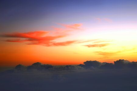 Brilliant orange skies hide above cloud line on flight between Kauai and the Big Island of Hawaii. Stock Photo - 15107494