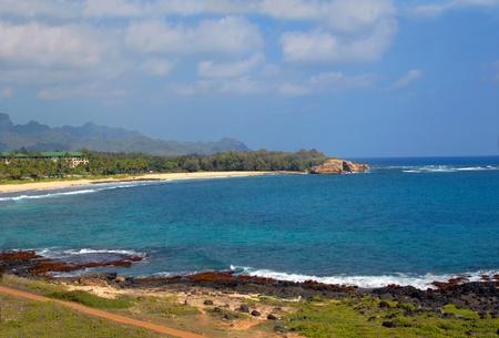 rocky point: Resort dispone di bellissima spiaggia a forma di mezzaluna e un aspro e roccioso, punto chiamato Makahuena Aqua marino oceano, montagne aspre Haupu sono incorniciati da cieli azzurri Archivio Fotografico
