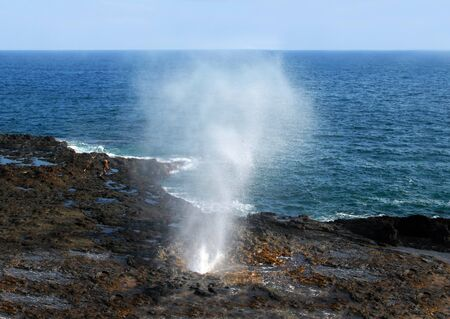 blow hole: Fishermen braves the ocean as he fishes the Spouting Horn a blow hole on the island of Kauai, Hawaii. Stock Photo