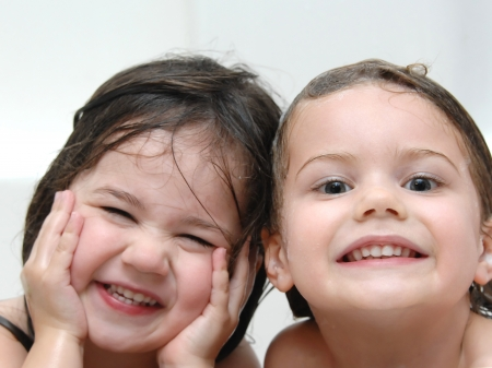 Two sisters laugh through bath time with wet heads and smiles.  Closeup shows one sister smiling and the other laughing.