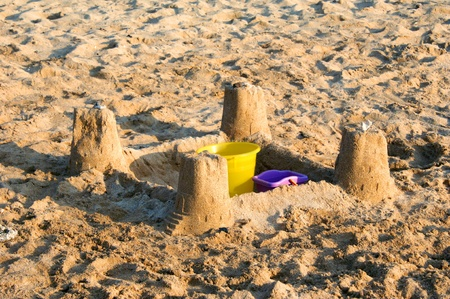 turreted: Four turreted sand castle is evidence of a fun day for a child on vacation on the island of Kauai, Hawaii.  Yellow and purple plastic pails sit inside sand castle.