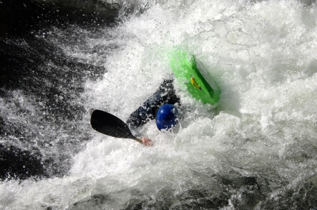rafter: Rafter fights raging water as he tries to keep his kayak afloat.  Kayak is bright green and man is wearing a blue helmet.