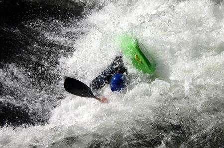 Rafter vecht woedende water als hij probeert om zijn kajak overeind te houden. Kayak is helder groen en man draagt een blauwe helm.
