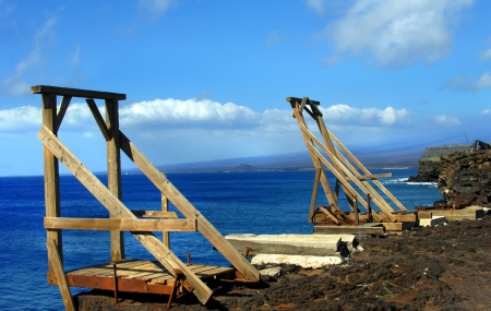 hoists: Two wooden canoe hoists perch on steep cliffs edge at South Point on the Big Island of Hawaii.  Vivid blue water