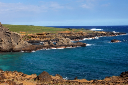 Green sand beach, Big Island of Hawaii, has tremendous scenery of rocky monoliths and rugged seashore.  Aqua blue waters turn to deep blue as it nears the distant horizon. photo