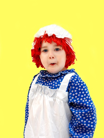raggedy: Little girl, dressed as a rag doll, gives expression to her amazement by the indrawn breath and facial expression   She is wearing a red yarn wig, mop hat, and pinafore style dress  Stock Photo