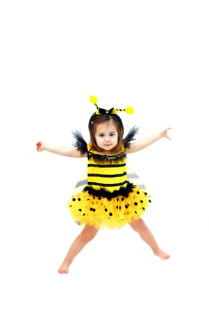 Little girl, dressed in bee costume, dances with her arms outstretched   She is wearing a bumble bee costume complete with wings and antenna  photo