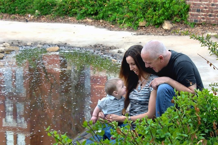 Baby is fascinated with his parent and looks straight into their eyes   They are sitting besides a small pool in downtown park in Wichita, Kansas  photo