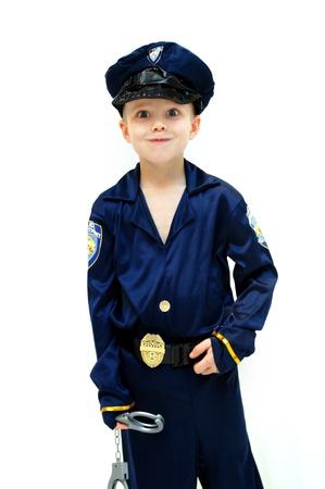 Kleine jongen, gekleed in politie geeft een felle blik Hij houdt een paar handboeien