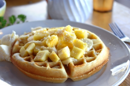 Hawaiian sunshine, walffles covered in chunks of pinneapple, banana and sprinkled coconut   Butter melts on the side and a fork waits to cut into this delicious breakfast