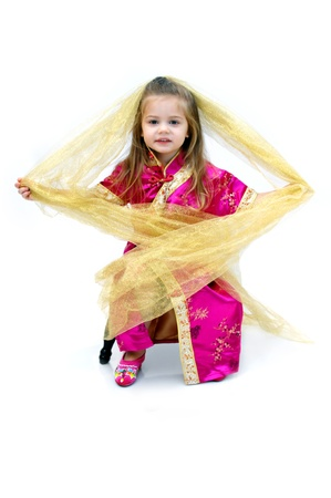 Small American girl wears a japanese style kimono costume to represent the mixture of American and Japanese cultures   Her costume is hot pink trimmed in gold with matching shoes   She has a gold scarf on her head  photo
