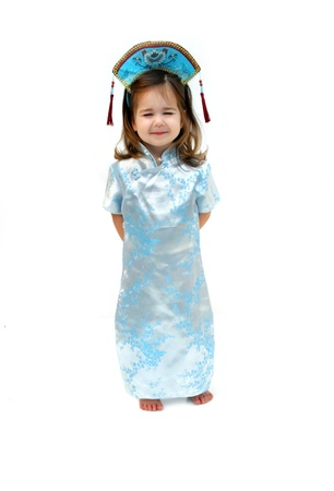 would: Little girl, wearing a kimono style silk dress and cap, squint to show what she thinks an oriental little girl would look like