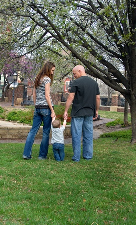 Mom and Dad help little infant to walk between them by holding his hands   Spring is blooming all around them and a robin sits in the grass besides them   Park is in downtown Wichita, Kansas  photo