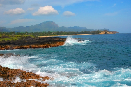 Keoneloa Bay shoreline is rugged and lava rock lined   The Haupu Range backdrops a beautiful landscape on the Island of Kauai, Hawaii  Banque d'images