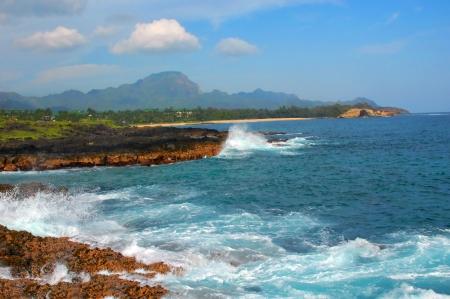 Keoneloa Bay shoreline is rugged and lava rock lined   The Haupu Range backdrops a beautiful landscape on the Island of Kauai, Hawaii  photo