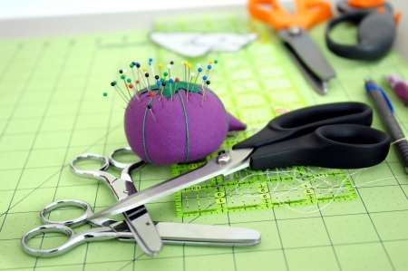Sewing tools of the trade lay on a green cutting matt   Pins are stuck in purple pin cushion and three pair of different sized scissors lay in a stack on table top  Banque d'images