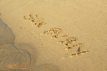 sunburn: Sunburn can ruin your dream vacation.  Hand written in the sand, the letters spell sun burn on Brennecke Beach, Kauai, Hawaii.