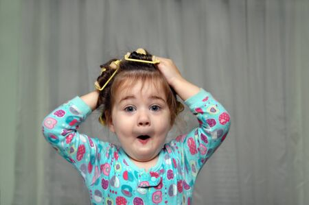 Old fashioned sponge curlers make this little girl want to pull them out.  She is making a comical face as she puts her hands on her head. Stock Photo - 15111533