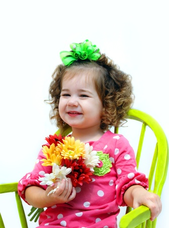 ringlets: Hot pink and polka dots fill shirt on little girl sitting in lime green rocking chair.  She is holding a bouquet of flowers and smiling.  Her hair is a mass of ringlets.