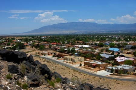 Overlook at the Petroglyph National Monument shows Albuquerque, New Mexico.  Sandia Mountains loom in the background and in the foreground black basalt boulders and a curving city street.