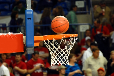 Crowded gymnasium watches a spinning basketball drop into the orange metal goal and white net