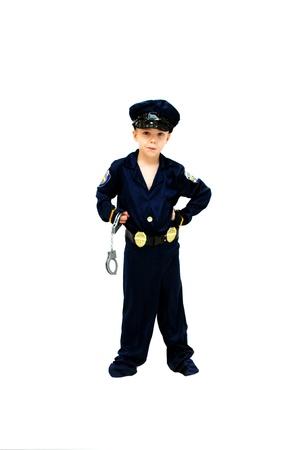 Kleine jongen, gekleed als een politieagent, is klaar om eventuele arrestatie Hij heeft een grimas op zijn gezicht te maken en houdt zijn handboeien