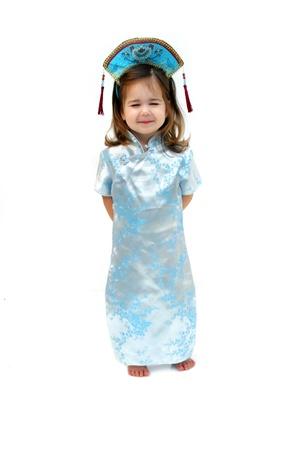 Kleines Mädchen trägt einen Kimono-Stil Seidenkleid und Mütze, schielen, um zu zeigen, was sie denkt, ein orientalisches Mädchen aussehen würde Standard-Bild - 15622635