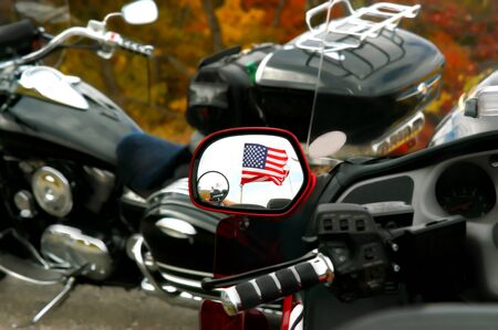 doubled: Photographer is captured in a doubled mirror image of American flag in the rear view mirror of motorcycle flying the American flag.