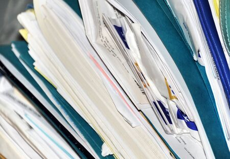 Stacks of blue folders and white papers form a large pile of medical records.  Pharmacy receipts protrude from folders and other paperwork.