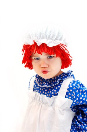 Angry and cross little girl is dressed in a rag doll costume.  Her hair is red yarn topped with a white mop hat.