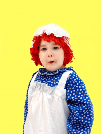 raggedy: Little girl, dressed as a rag doll, gives expression to her amazement by the indrawn breath and facial expression.  She is wearing a red yarn wig, mop hat, and pinafore style dress.