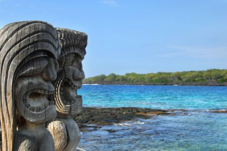 Two wooden hawaiian carvings look out over the blue waters of Honaunau Bay at the Puuhonuaa O Honaunau National Historical Park on the Big Island of Hawaii.