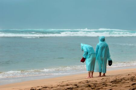 they are watching: Two tourists brave the wet to walk barefoot on Kee Beach on the Island of Kauai.  They are both wearing turquoise rain coats and watching the waves.