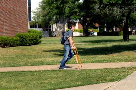 Young man struggles to get to his college classes while walking on crutches   Backpack rides on his back